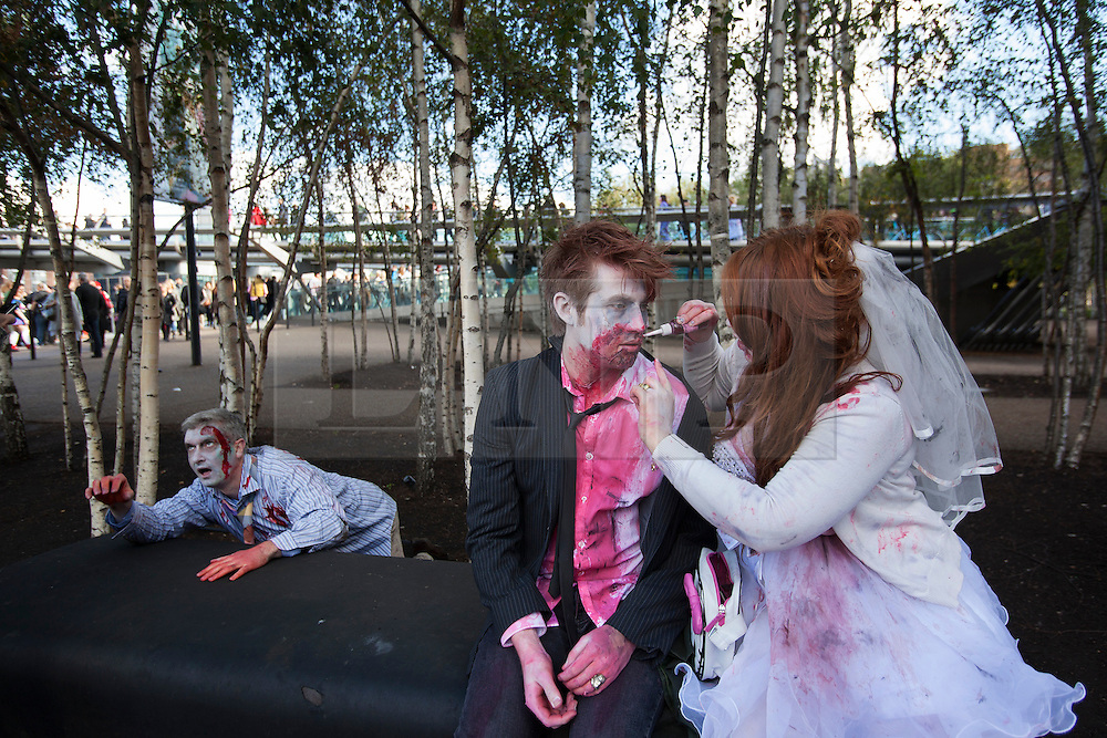© licensed to London News Pictures. London, UK 13/10/2012. People with zombie costumes and make-ups getting ready for World Zombie Day in Southbank, London as more than 2,000 'zombies' celebrating World Zombie Day in London on 13/10/12. Photo credit: Tolga Akmen/LNP