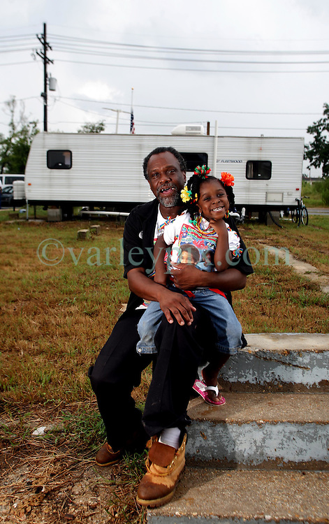 29 August 2007. Lower 9th Ward, New Orleans, Louisiana. <br /> Second anniversary of Hurricane Katrina. Robert Lynn Green Sr  and grand daughter Chayana Hurst (4 yrs) sits on the steps of 1826 Tennessee Street in front of his trailer in the Lower 9th Ward. The steps are all that remain of his house after it was deluged by the levee breach just blocks from the steps. Robert lost his mother and grand daughter at the house when they perished in the terrible flooding. He lost hold of his grand daughter in the swirling floods. She was drowned. His mother was not found for 4 months when her skeleton was discovered in what remained of his washed away house. Robert hopes to rebuild. Many residents are struggling to return to the still derelict and decimated Lower 9th Ward.<br /> Photo credit©; Charlie Varley/varleypix.com