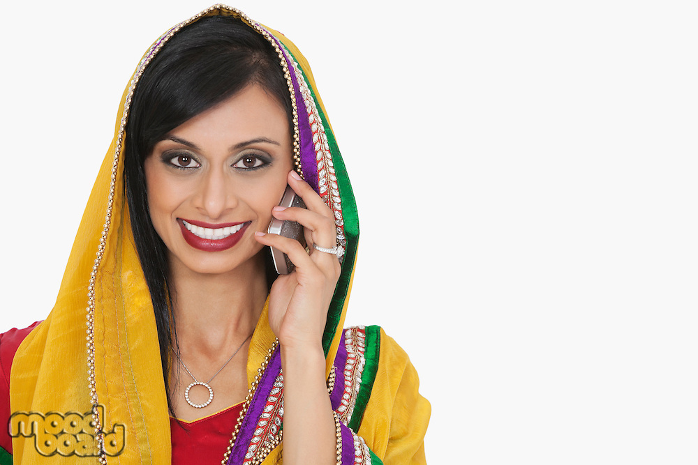 Portrait of an attractive Indian woman in traditional wear answering phone call over gray background