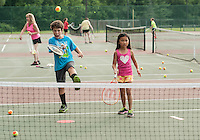 Mark Dayn with a mean forehand shot paired with Sophia Moore during tennis lessons at Memorial Park on Tuesday evening.  (Karen Bobotas/for the Laconia Daily Sun)