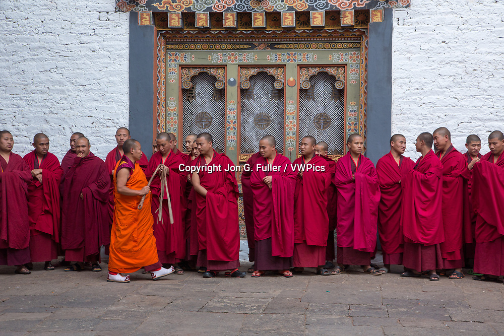 A line of Buddhist monks gather for a ceremony in the religious courtyard of the Punakha Dzong in Punakha, Bhutan.  A monk in saffron robes wearing tsholham, traditional knee-length boots and carrying a whip supervises.