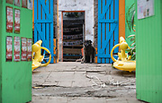 A black dog sits by the door at the entrance to a colorfully painted shop.