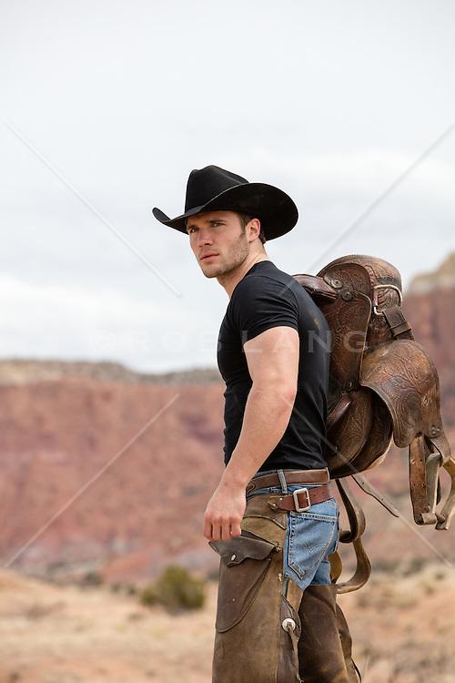 cowboy walking with a saddle on a mountain range
