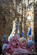 As Prime Minister Theresa May tours European capitals hoping to persuade foreign leaders to accept a new Brexit deal (following her cancellation of a Parliamentary vote), pro-EU Remainers protest with satirical figures beneath the statue of King George V beneath Westminster Abbey and opposite the Houses of Parliament, on 11th December 2018, in London, England. The figures depict (L-R) David Davies, Michael Gove, Boris Johnson and Theresa May.