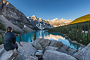A young woman views the sunrise over the scenic panoramic view of a blue sky over the turquoise waters at Lake Louise and the snow dusted Fairview Mountain in Banff National Park in Alberta, Canada.