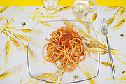 amatriciana bucatini in glass dish view from above on table cloth with spikes garnish, italian traditional food
