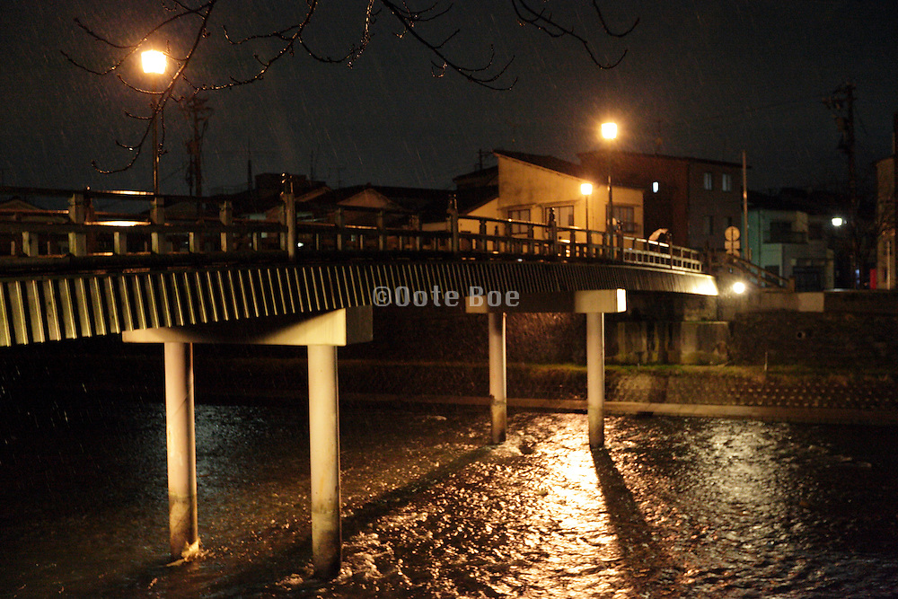 heavy rain storm after dark with river and bridge