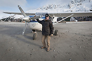 Zack Tappan, cheif pilot at Homer Air stands beside the cessna 206 bushplane on a remote beach in the Kenai Fjords during a flightsee adventure from Homer, Alaska.