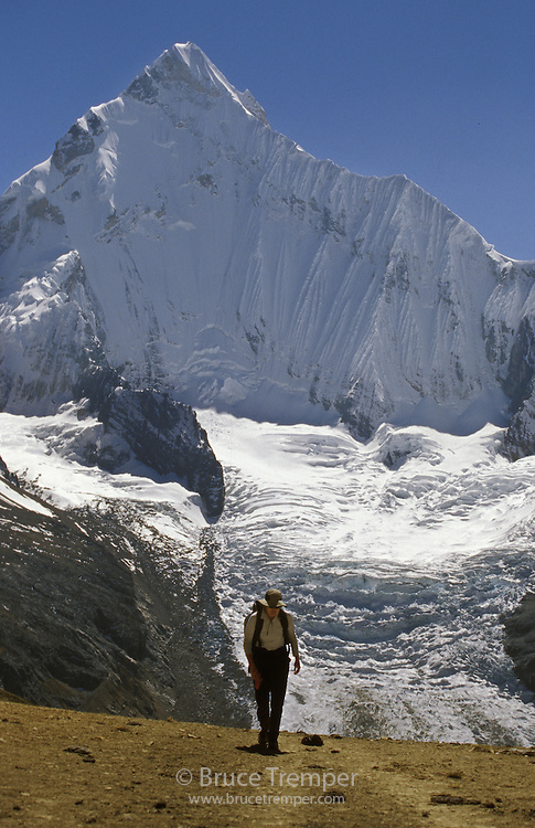 Susi Hauser trekking over a high pass in the spectacular Huayhuash Range of Peru with Yerupaja looming above.