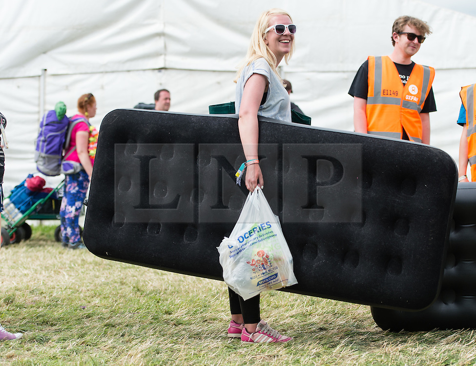 © Licensed to London News Pictures. 24/06/2015. Pilton, UK.   A festival goers arriving at Glastonbury Festival carrying an inflatable mattress.   Today is a warm sunny afternoon on  Wednesday Day 1 of the festival.        The pedestrian gates to the festival opened at 8am this morning, with many festival goers arriving and waiting throughout last night for the opening.  This years headline acts include Kanye West, The Who and Florence and the Machine, the latter having been upgraded in the bill to replace original headline act Foo Fighters.  Photo credit: Richard Isaac/LNP
