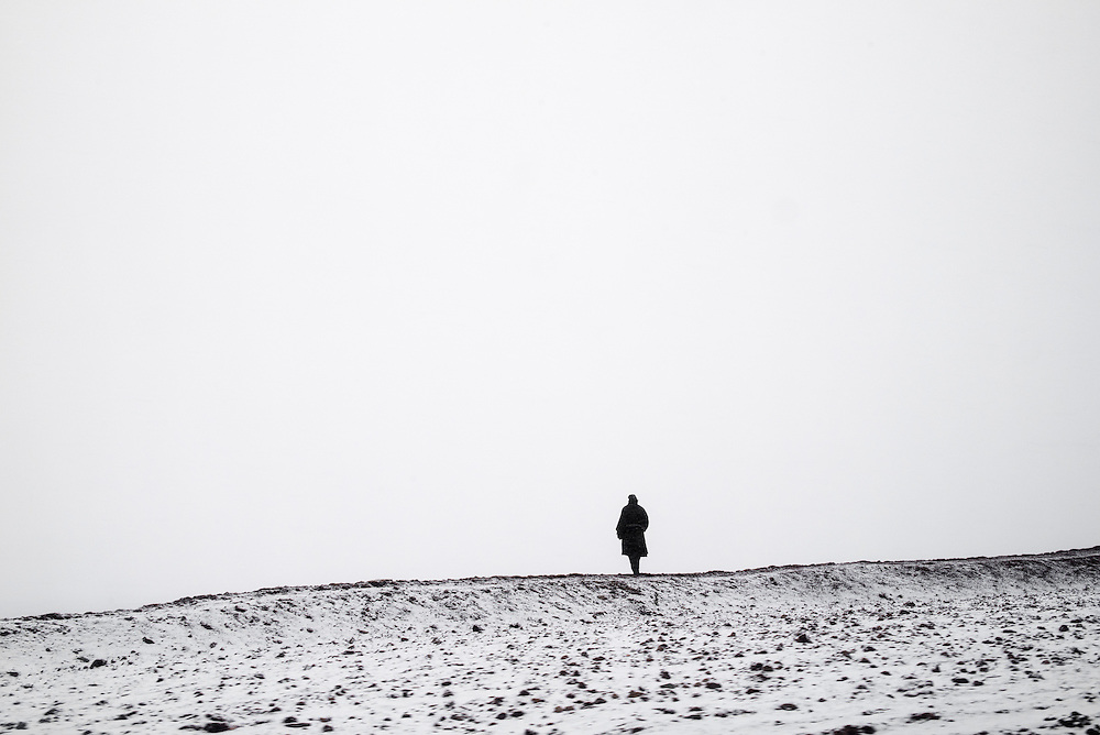 A nomad is silhouetted against a snowstorm near Yushu prefecture, Tibet (Qinghai, China).
