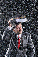 Businessman covering head with binder running through rain