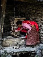 Woman milling grain by a stream near Swanta village.