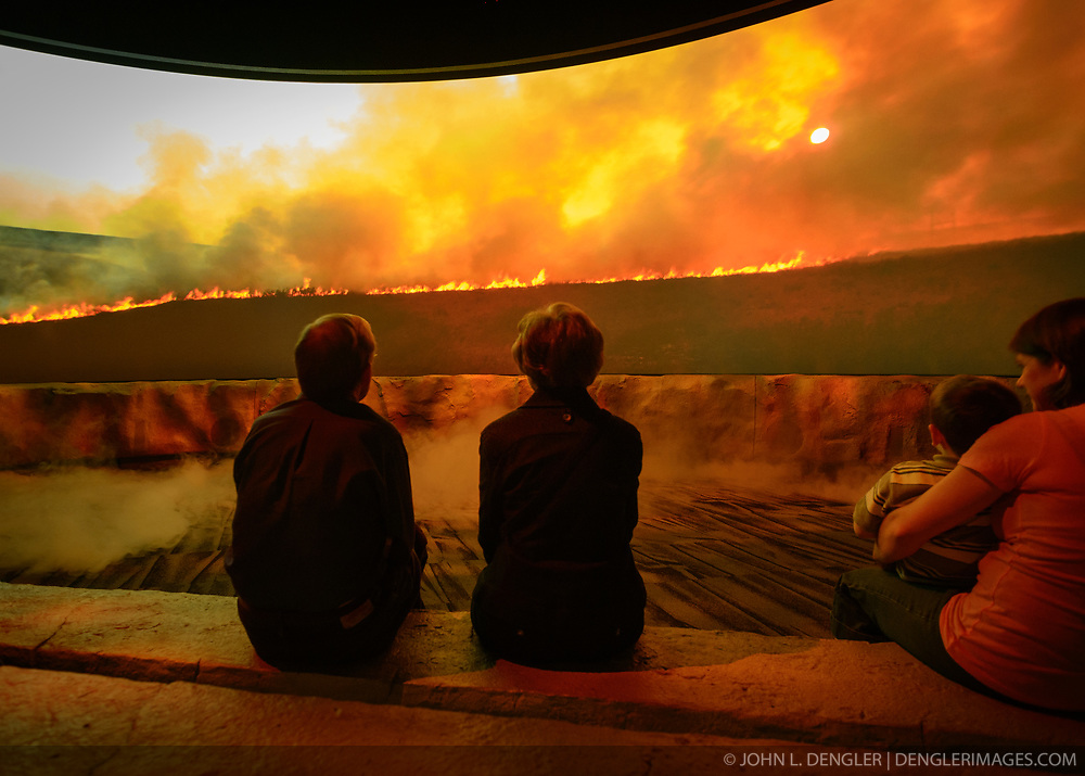 Visitors to the Flint Hills Discovery Center watch the 15-minute 'immersive experience' film which has special effects such as smoke, fog, mist and wind which appear in the theater as the high definition film is shown on a large panoramic screen at the $24.4 million center, located in Manhattan, Kansas. This scene in the movie depicts the important role that fire plays in preserving the tallgrass prairie ecosystem. Through interactive exhibits, Flint Hills Discovery Center visitors can explore the science and cultural history of the last stand of tallgrass prairie in North America – one of the world's most endangered ecosystems. Other attractions of the Flint Hills Discovery Center include: an 'underground forest' depicting the long roots of prairie plants including the 7-foot roots of bluestem prairie grass; explanations of importance of fire to the Flint Hills tallgrass prairie; and exhibits about the people and cultural history of the Flint Hills. The Flint Hills Discovery Center was designed by the museum architectural firm Vern Johnson Inc. with interpretive design and planning by Hilferty and Associates. The 34,900 square foot science and history learning center features permanent interactive exhibits, temporary exhibits, and areas for community programs and outreach activities. The Flint Hills Discovery Center received a LEED green building certification for their environmental design and energy efficiency, including their lighting and geothermal heating/cooling system.