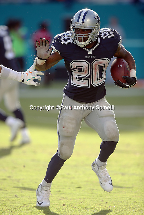 Dallas Cowboys running back Darren McFadden (20) straight arms a defender as he burns the fourth quarter clock while running the ball during the 2015 week 11 regular season NFL football game against the Miami Dolphins on Sunday, Nov. 22, 2015 in Miami. The Cowboys won the game 24-14. (©Paul Anthony Spinelli)