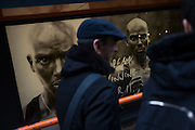 Passers-by walk past British athlete Mo Farah's face adorns posters in a Nike shop window in London's west end.