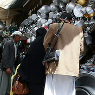 Yemen, Sanaa Souq, man carrying a Kalashnikov in front of a crockery shop. When in public, women are usually accompanied by a male, as pictured here at the market in Sanaa.