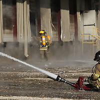 Furemen do what they can from outside to try and conatin the fire at American Furniture in Ecru Friday.
