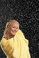 Smiling Woman Wrapped in Towel Standing in Rain