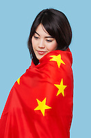 Patriotic young woman wrapped in Chinese flag over blue background
