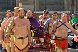 © Licensed to London News Pictures. 26/08/2017. London, UK. A man dressed as Emperor Hadrian is brought into the arena as members of the Brittania re-enactment group put on Gladitorial Games in Guildhall Yard, the site of London's only Roman Amphitheatre.  The Gladiator Games will be entertaining crowds over the August Bank Holiday Weekend. Photo credit : Stephen Chung/LNP