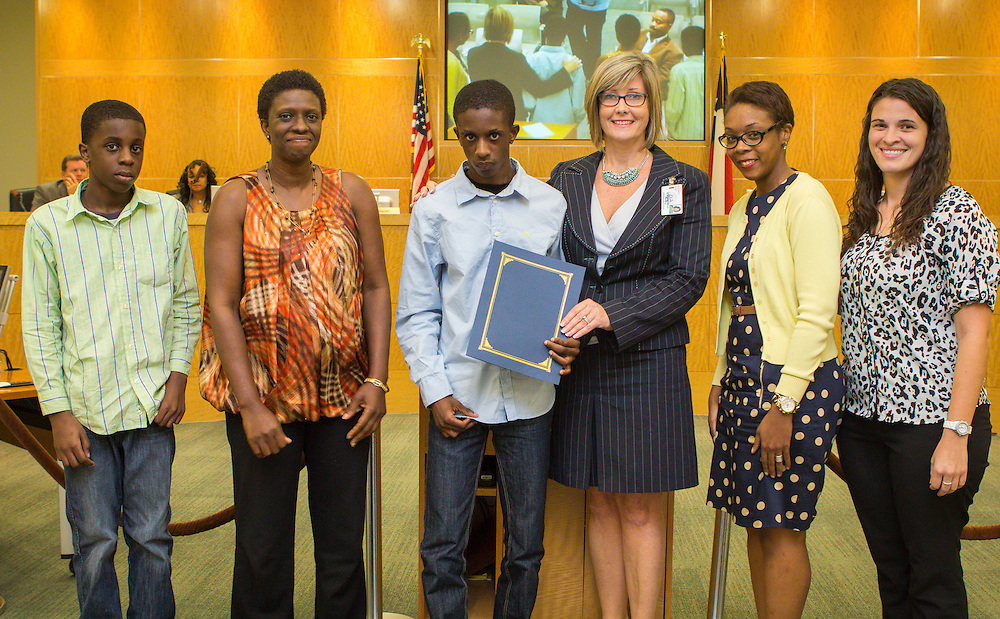 Westside High School principal Peggi Stewart, center, flanked by staff, poses for a photograph with student Barinem Lenu, center, flanked by family, after Lenu was awarded a citation during the Board of Education meeting, October 10, 2013.