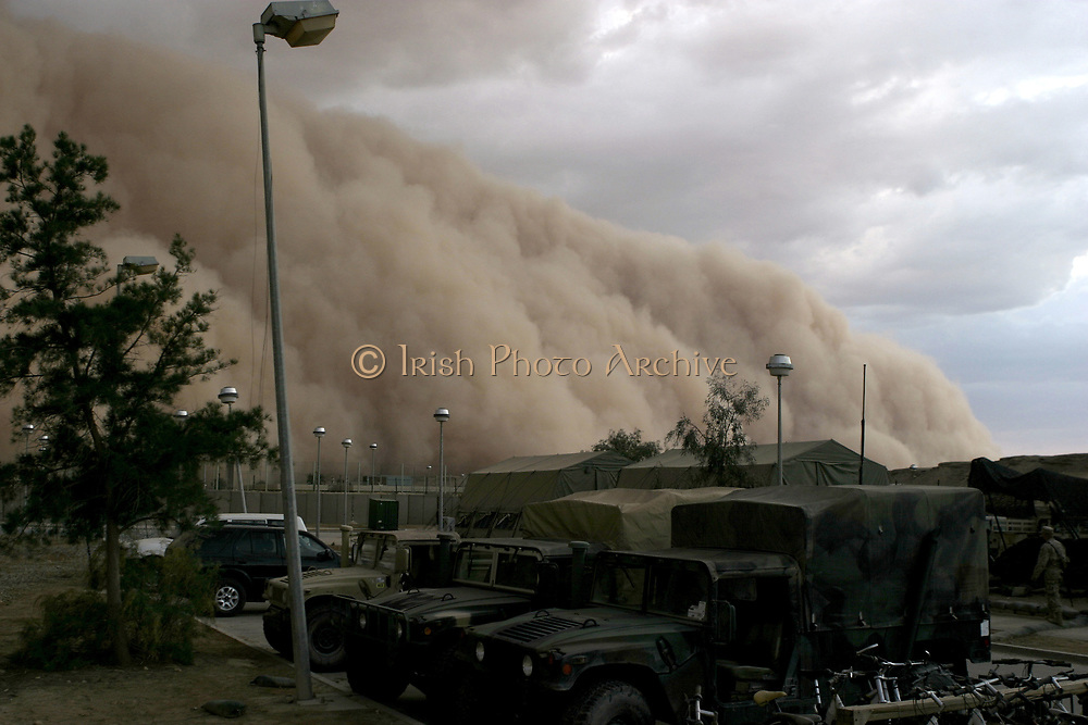 Dust storm cloud (haboob) is close to enveloping a military camp as it rolls over Al Asad Iraq 2005.