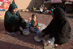 Licensed to London News Pictures. 22/10/2016. Three  Iraqi IDPs, newly arrived from areas where the Mosul Offensive is taking place, eat their food in a school at the Dibaga refugee camp near Makhmur, Iraq. Upon arriving at the camp women and children stay in the school for around 10 - 15 days whilst completing the registration process.<br />