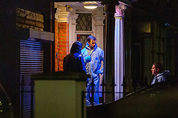 © Licensed to London News Pictures. 20/01/2020. London, UK. A forensic investigator stands in a property doorway that is being searched as police cordon off a road and park approximately half a mile from the location where an investigation was launched into the deaths of three men in Redbridge, all of whom had suffered apparent stab injuries.. Photo credit: Peter Manning/LNP