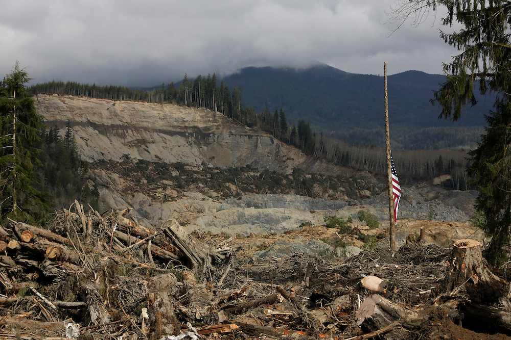 A flag is pictured at half staff in the foreground of a collapsed hillside from a massive mudslide that struck Oso near Darrington, Washington April 2, 2014. Efforts to recover bodies following a Washington state mudslide that killed at least 29 people could be hampered in the coming weeks if melting snow runs into a clogged river at the disaster site, officials said. Over the past two days, workers at the mud pile in the foothills of the Cascade Mountains, northeast of Seattle, have taken advantage of sunny skies and receding water, but more rain is expected from Thursday through Sunday.  REUTERS/Jason Redmond (UNITED STATES)