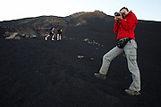 Woman taking photos while climbin up Pico Fogo, Fogo Island, Cape Verde, West Africa.