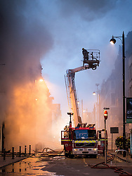 © Licensed to London News Pictures . 13/07/2013 . Manchester , UK . An elevated platform is used to examine the scene from above . A fire fighter is dead and two 15 year old girls are under arrest on suspicion of manslaughter after a blaze in Manchester yesterday (Saturday 13th July) . More than 60 fire fighters tackled a blaze at Paul's Hair World on Oldham Street in Manchester City Centre late in to the night (Saturday 13th July 2013) . Twelve crews from four stations were deployed . Several streets in a block in the city centre are sealed off . Photo credit : Joel Goodman/LNP