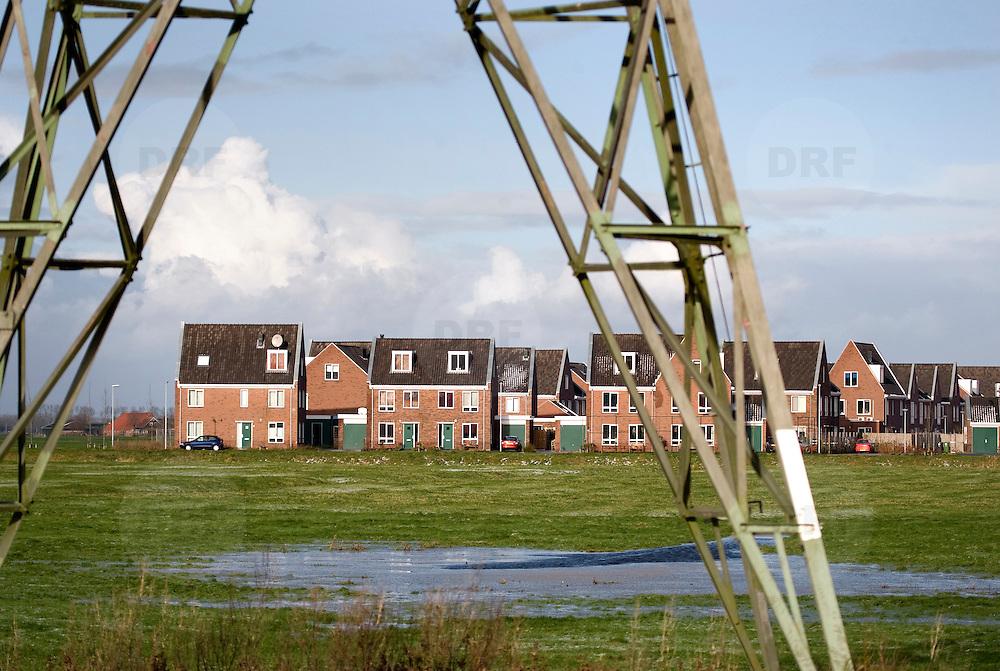 Nederland Groningen 22 november 2008 20081122 Foto: David Rozing ..Nieuwbouw woningen aan de rand van Groningen, westzijde,  gelegen tegen polder gebied/ groene omgeving. Op de voorgrond een elektriciteitsmast. ..Gezondheid.1. Zijn de elektromagnetische velden van de hoogspanningsmasten schadelijk voor de gezondheid?.Omdat er mogelijk een verband is tussen elektromagnetische velden en gezondheidsklachten bij kinderen, gelden er nieuwe strenge regels. De Staatsecretaris van VROM heeft aangegeven (vanuit het voorzorgsprincipe) dat kinderen niet langdurig mogen verblijven in een gebied waar de magnetische veldsterkte hoger is dan 0,4 microtesla (microtesla is de eenheid waarin de sterkte van het magneetveld wordt uitgedrukt)...2. Is de combinatie van fijnstof in de lucht en hoogspanningslijnen schadelijk voor de gezondheid?.Er zijn onderzoeken die aantonen dat de combinatie van fijnstof in de lucht en hoogspanningslijnen mogelijk schadelijk is voor de gezondheid. Er zijn echter ook onderzoeken die dit relativeren. Het ministerie van VROM laat hier aanvullend onderzoek naar doen omdat op dit moment nog niet duidelijk is of de combinatie fijnstof/hoogspanning schadelijk is voor de volksgezondheid...Foto David Rozing