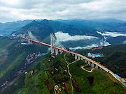 BIJIE, CHINA - SEPTEMBER 10: <br /> <br /> Aerial view of the Beipan River expressway bridge (or Beipanjiang bridge) under construction on September 10, 2016 in Bijie, Guizhou Province of China. The 1,341.4-meter-long Beipan River expressway bridge has a height equivalent to a 200-story building, which makes it the world\'s highest bridge down to the ground or water surface. The bridge spanning the Beipanjiang Valley was started to build in 2013 and completed the main connection on September 10, 2016.<br /> ©Exclusivepix Media