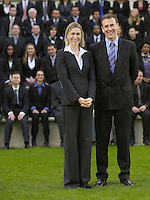 Business couple standing in front of business people sitting on tribune portrait