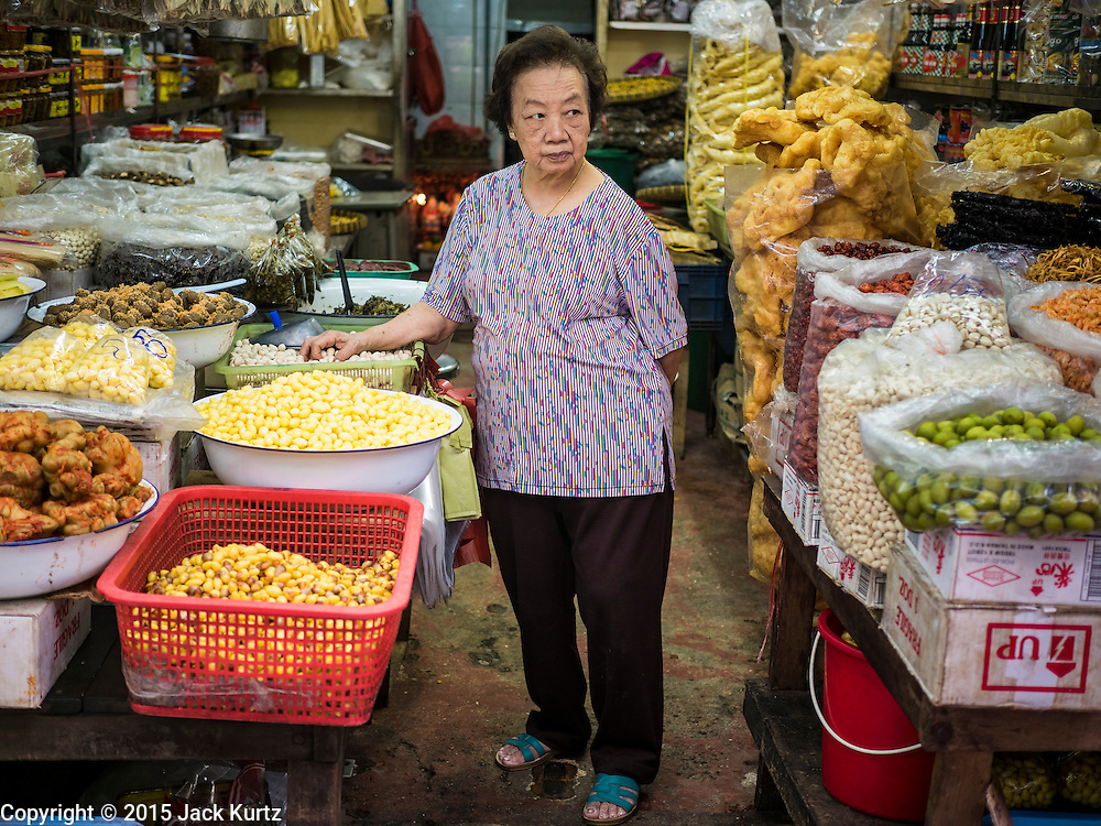 28 AUGUST 2015 - BANGKOK, THAILAND: A woman gets ready to close her shop early on Hungry Ghost Day in Bangkok's Chinatown. Mahayana  Buddhists believe that the gates of hell are opened on the full moon of the seventh lunar month of the Chinese calendar, and the spirits of hungry ghosts allowed to roam the earth. These ghosts need food and merit to find their way back to their own. People help by offering food, paper money, candles and flowers, making merit of their own in the process. Hungry Ghost Day is observed in communities with a large ethnic Chinese population, like Bangkok's Chinatown.     PHOTO BY JACK KURTZ