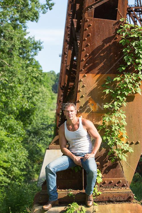 hot man sitting under a railroad trestle