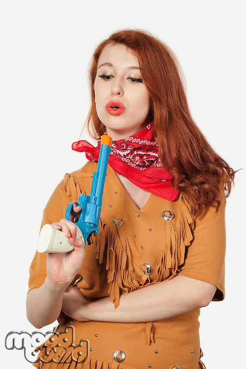 Young cowgirl with toy pistol against gray background