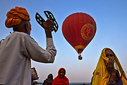 Finding the balloon ride to be risky, a religious person chants for the safe journey of the riders at a fair in Rajasthan . In India tradition and modernity go hand in hand.