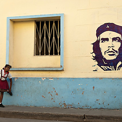 Girl in a school uniform close to a painting of Che Guevara, Camaguey, Cuba, Caribbean.