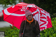 The umbrella provides protection from the rain while a scarf potentially protects from teh virus - The first heavy rain doesn't stop, but greatly reduces, outdoor activity around Clapham Common. The 'lockdown' continues for the Coronavirus (Covid 19) outbreak in London.