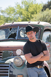 cowboy leaning against an old pick up truck
