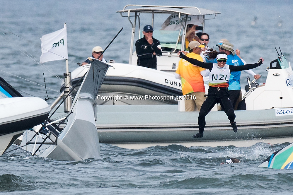 New Zealand's Alex Maloney jumps from her boat after winning Silver for the 49er class sailing race the 2016 Rio Olympics on Thursday the 18th of August 2016. © Copyright Photo by Marty Melville / www.Photosport.nz