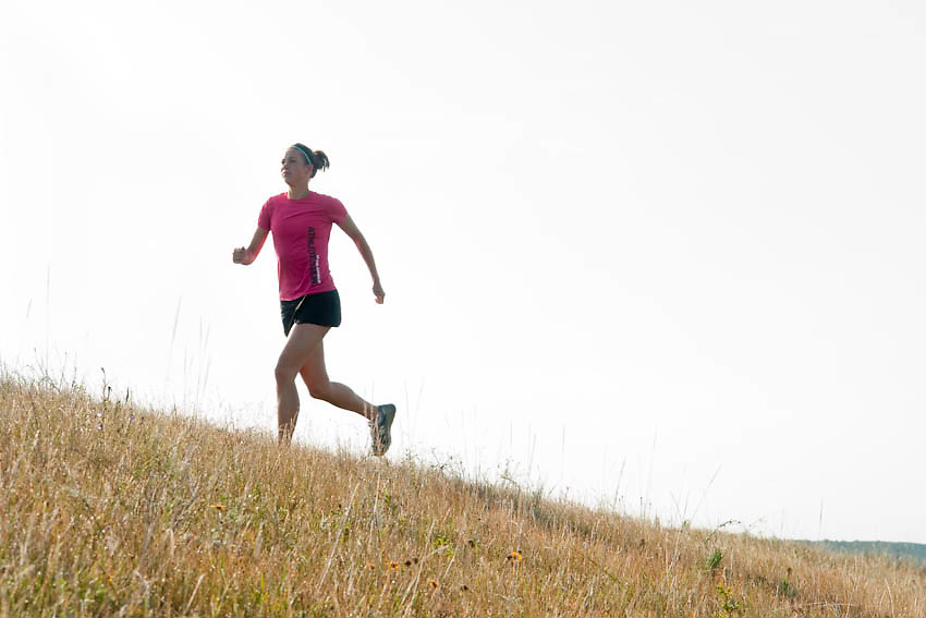 Female runner running through a grass field Manitoba, Canada.