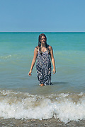a girl standing in a lake in the waves