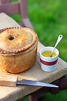 Pork pie knife and cup of mustard on table outdoors