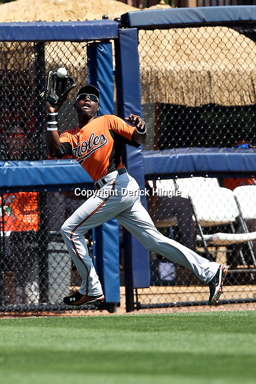 March 20, 2011; Port Charlotte, FL, USA; Baltimore Orioles center fielder Adam Jones (10) catches a fly ball during a spring training exhibition game against the Tampa Bay Rays at Charlotte Sports Park.  Mandatory Credit: Derick E. Hingle-US PRESSWIRE