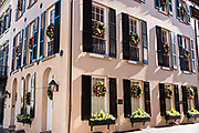 A historic building decorated with a Christmas wreaths on each window along Broad Street in Charleston, SC.