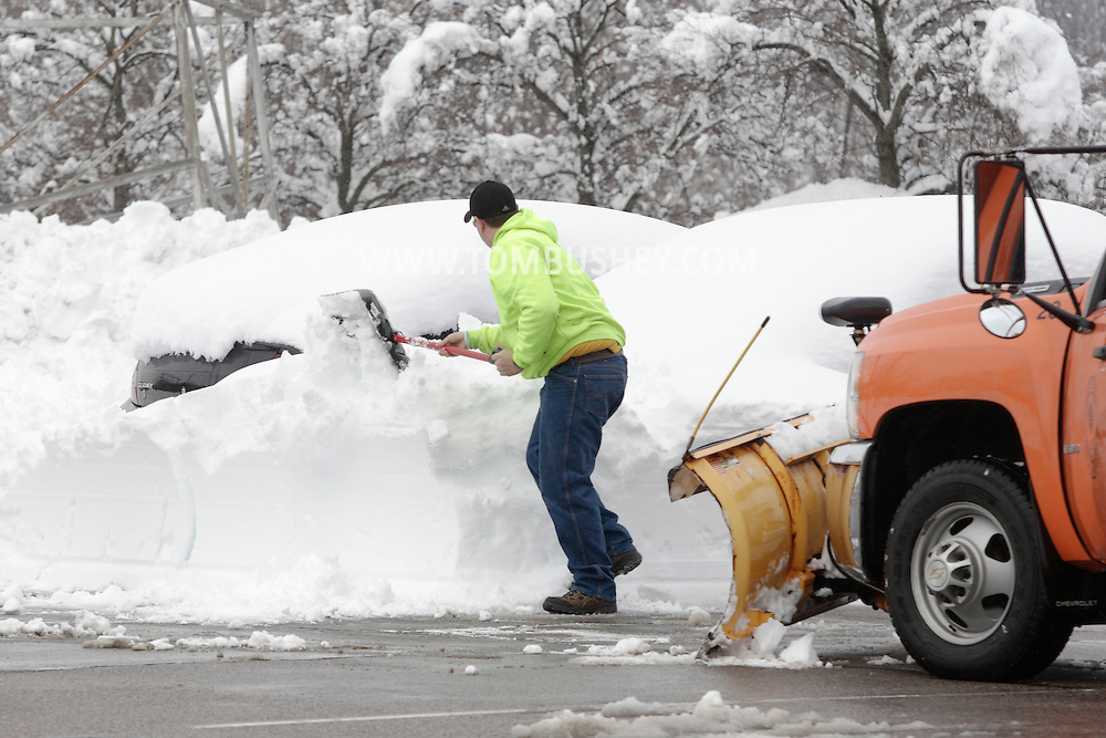 Monroe, New York - An Orange County worker removes snow around a car with a shovel in a commuter parking lot the morning after a storm dropped 31 inches of snow. Feb. 27, 2010.