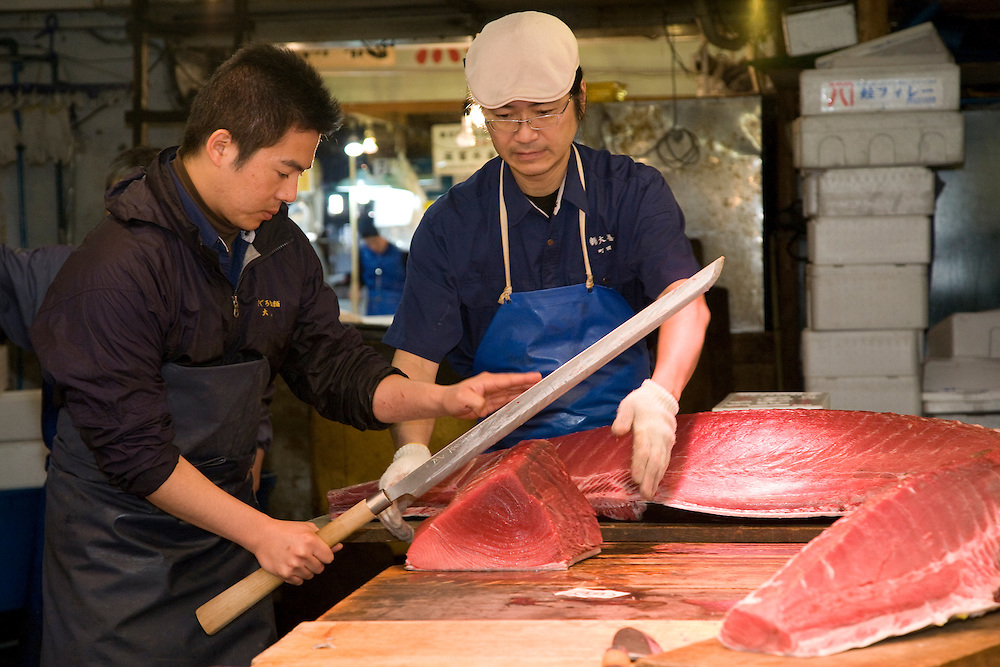Asia, Japan, Tokyo, men slicing tuna with long knife at Tsukiji Fish Market